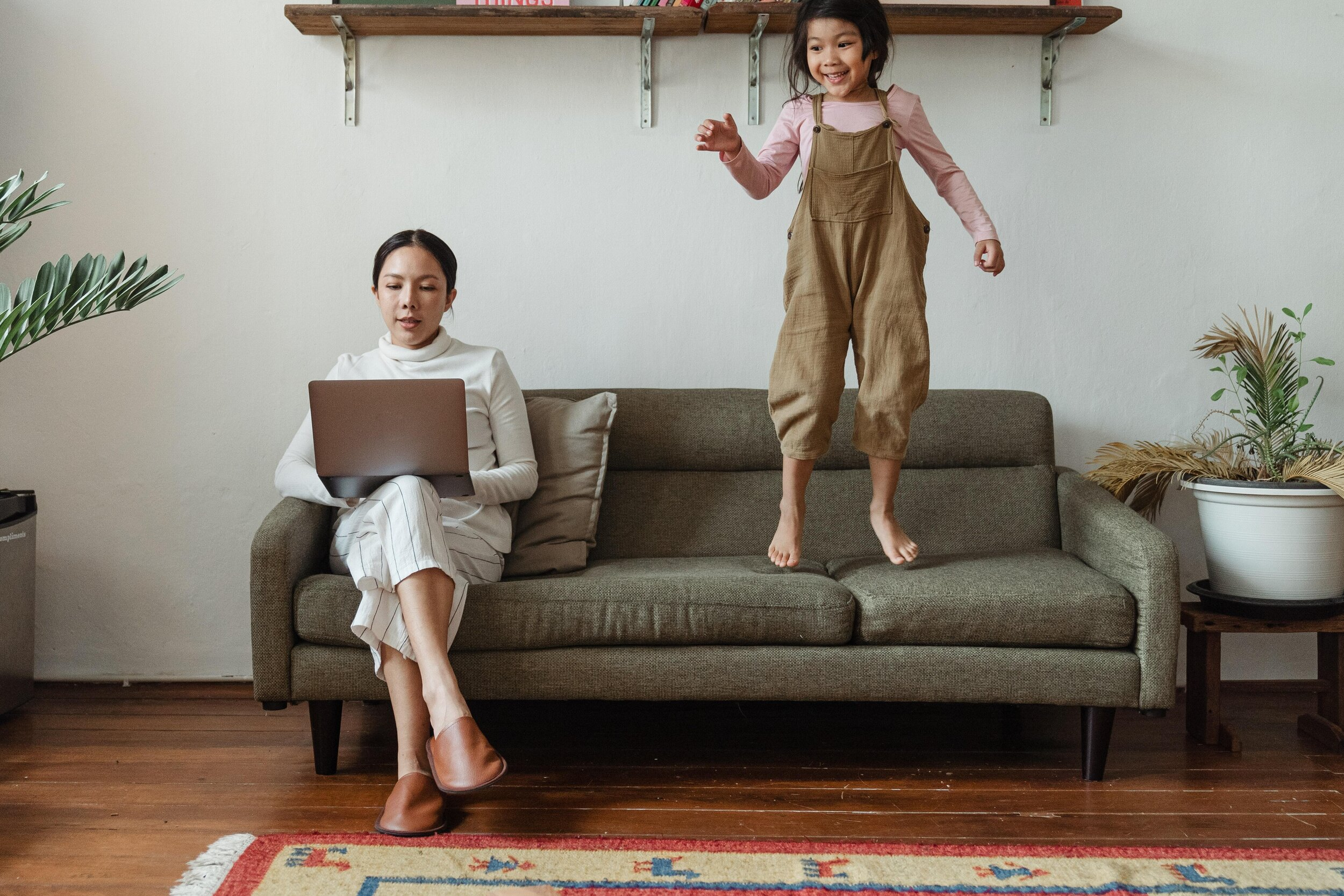 woman working on lounge with laptop, while daughter jumps on lounge next to her